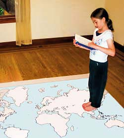 Girl walking on a map of the continents, reading a book.